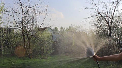 Watering The Garden Against The Setting Sun stock footage