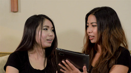Young Female Friends Talking And Reading On A Tabl stock footage