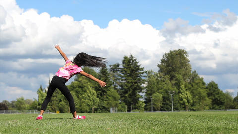 Cute Asian Girl Doing Cartwheels On The Grass Footage