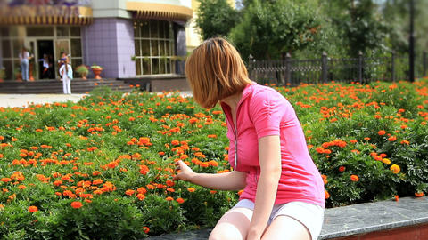 Young girl looking at marigold flowers Stock Video Footage