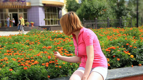 Young girl looking at marigold flowers Footage