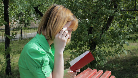 Young girl reading book and talking on phone Footage
