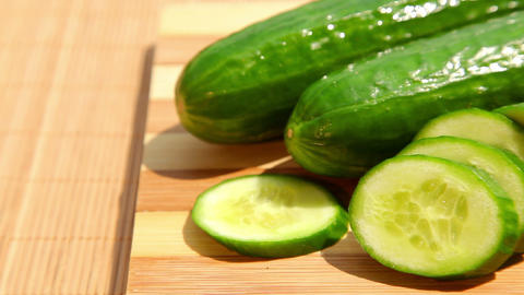 Cucumbers and cucumber slices on cutting board Stock Video Footage