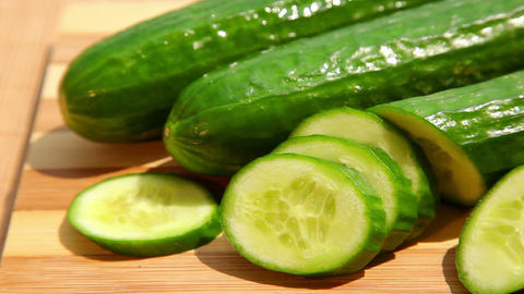 Cucumbers and cucumber slices on cutting board Footage