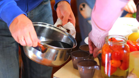 Pouring hot mulled wine from the pot into the cups Footage