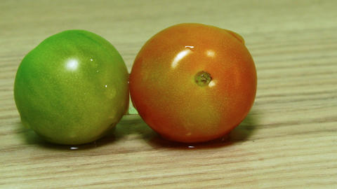 Dolly shot of two tomatoes on the wooden desk tabl Footage