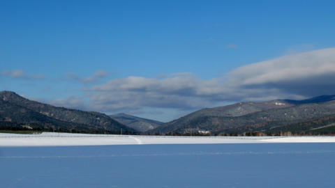 Time lapse of winter snow field, mountain and clou Stock Video Footage