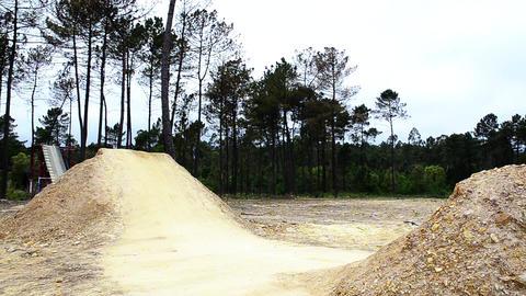 BMX biker jumping dirt jumps Live Action