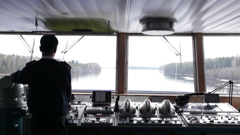 Navigation officer driving the ship on the river Stock Video Footage