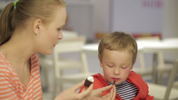 Mom feeds her son in restaurant Stock Video Footage