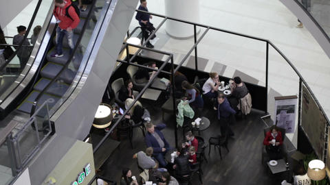 People eat in the cafe and go up and down on the e Stock Video Footage