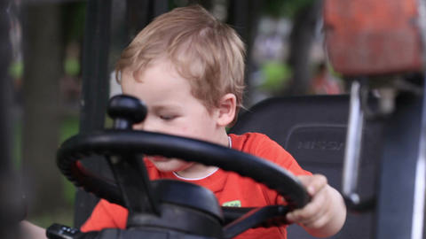 Kid Turns The Wheel Of The Tractor stock footage