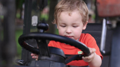 Kid turns the wheel of the tractor Stock Video Footage
