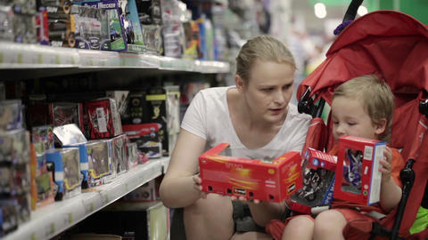 Mother and her two year old son are shopping for t Footage