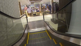 Shopping center area riding down escalator to the Stock Video Footage