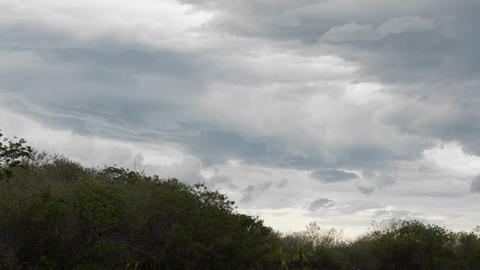 Storm clouds appear over a hilly landscape Stock Video Footage