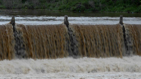 Flood waters rush over the side of a dam Footage