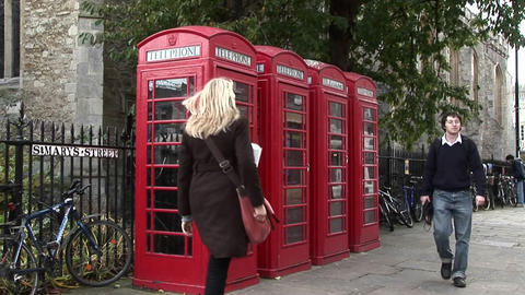 Red phone booths line a road in the UK Stock Video Footage