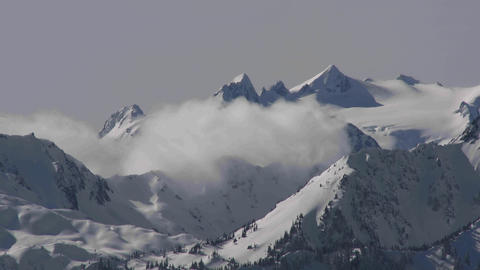 A time lapse shot of clouds over a snowy mountain Footage