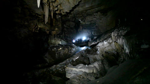 People explore a dark cave with flashlights Stock Video Footage