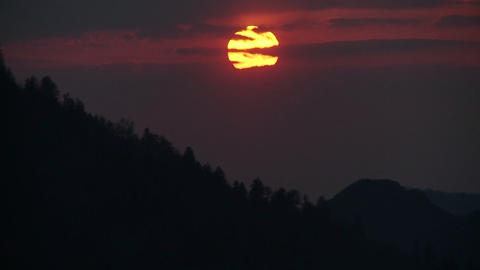 The sun slowly sets through the clouds behind a si Stock Video Footage