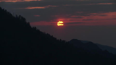 The sun slowly sets through the clouds behind a si Footage