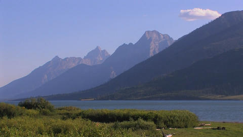A wilderness lake and layers of mountains Stock Video Footage