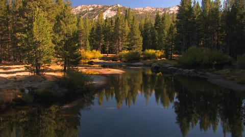 A mountain lake reflects the surrounding trees in Stock Video Footage