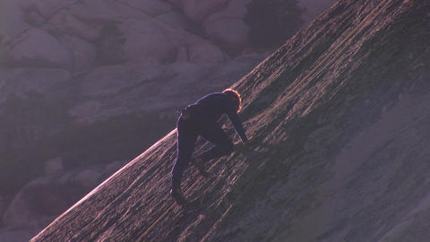 A man climbs up a steep slate of rock Stock Video Footage