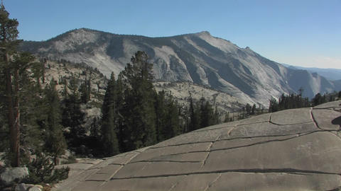 Trees stand among mountains and rocky hillsides at Stock Video Footage