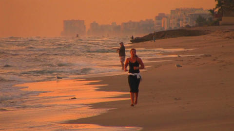 A woman jogs on the beach during golden-hour while Stock Video Footage