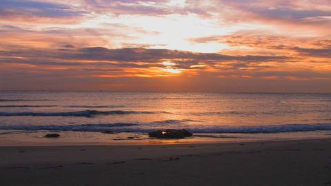 Beach waves slowly break during sunset Footage
