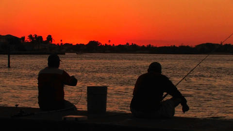 The silhouette of two men fishing at sunset Footage