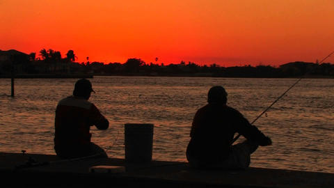 The silhouette of two men fishing at sunset Stock Video Footage