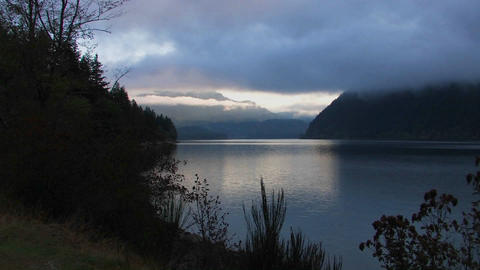 Clouds above a lake surrounded by trees at dusk Stock Video Footage