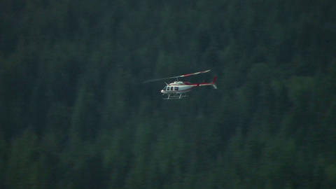 A helicopter flies over forested hills at Mt. St. Stock Video Footage