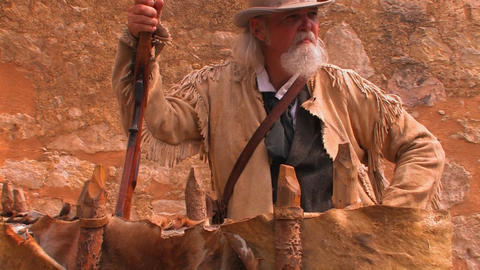 An old man holds a rifle and wears a leather pione Stock Video Footage