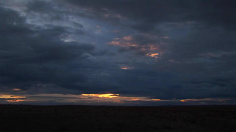 A time lapse of dark clouds at sunset Live Action