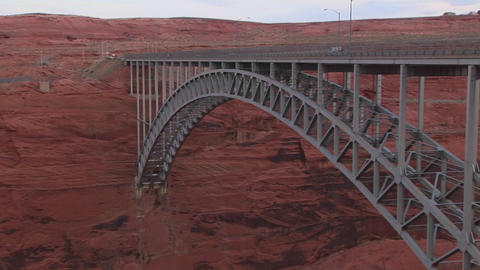 A metal bridge connects to a red and rocky mountai Footage
