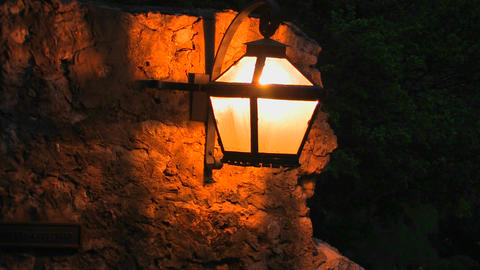 A light fixture attached to a stone wall is on at Stock Video Footage