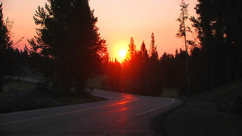 Sunrise over a road with a Subaru passing Stock Video Footage