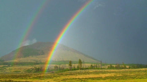 A double rainbow shines over a field Stock Video Footage