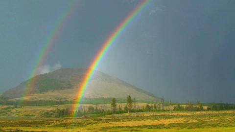 A double rainbow shines over a field Footage