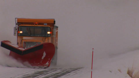 A snowplow works on a road in heavy winter snow Stock Video Footage