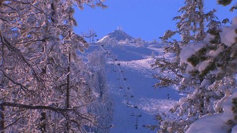 The chairlift at a busy ski resort is seen through Stock Video Footage