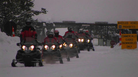 A snowmobile train heads through deep snow in Yell Footage