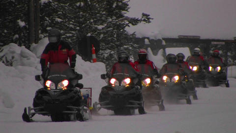 A snowmobile train heads through deep snow in Yell Stock Video Footage