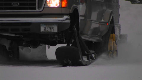 A snowplow truck moves along a snowy road Footage