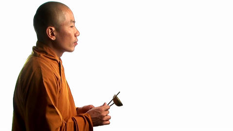 A Buddhist monk wearing an orange robe taps a bell Stock Video Footage