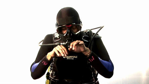 A scuba diver pretends to swim and check his depth Stock Video Footage